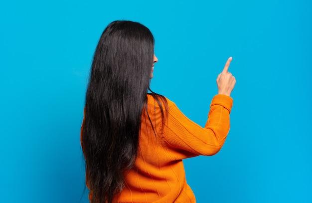 Młoda ładna latynoska kobieta stojąca i wskazująca na obiekt na przestrzeni kopii, widok z tyłu