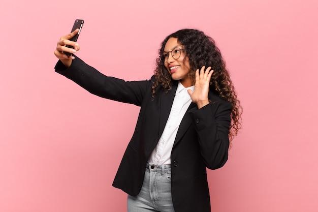 Młoda ładna latynoska kobieta. szczęśliwa i zdziwiona koncepcja biznesu ekspresji i smartfona