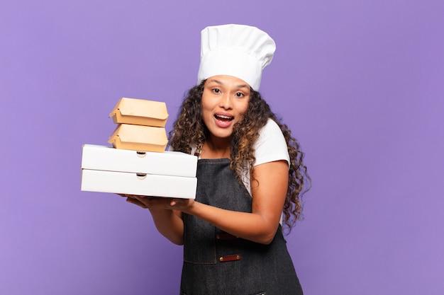 Młoda ładna latynoska kobieta. szczęśliwa i zdziwiona koncepcja szefa kuchni z grilla