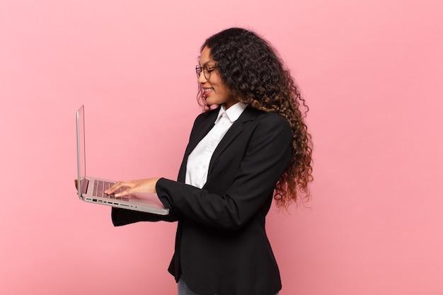 Młoda ładna latynoska kobieta. szczęśliwy i zaskoczony biznes wypowiedzi i laptop cpncept