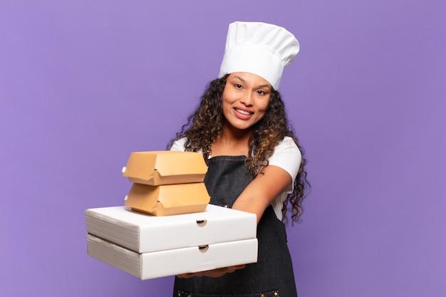 Młoda ładna latynoska kobieta. szczęśliwy i zaskoczony koncepcja szefa kuchni z grilla