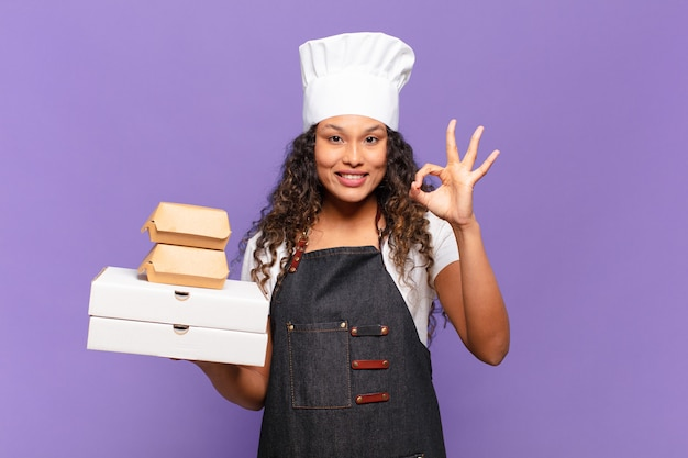 Młoda ładna latynoska kobieta. szczęśliwy i zaskoczony wyrażenie koncepcja szefa kuchni grilla
