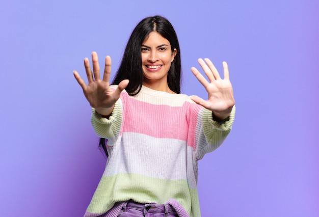 Młoda ładna Latynoska Kobieta Uśmiecha Się I Wygląda Przyjaźnie, Pokazując Numer Dziesięć Lub Dziesiątą Z Ręką Do Przodu, Odliczając W Dół Premium Zdjęcia