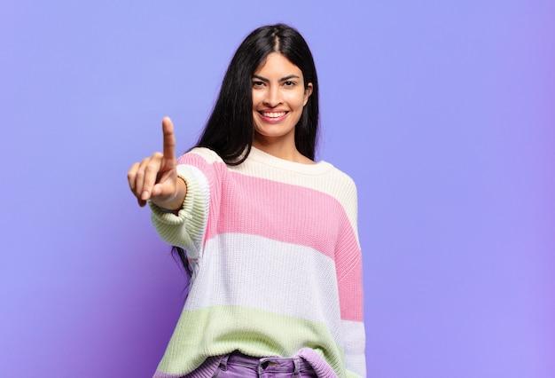 Młoda ładna latynoska kobieta uśmiecha się i wygląda przyjaźnie, pokazując numer jeden lub pierwszy z ręką do przodu, odliczając w dół