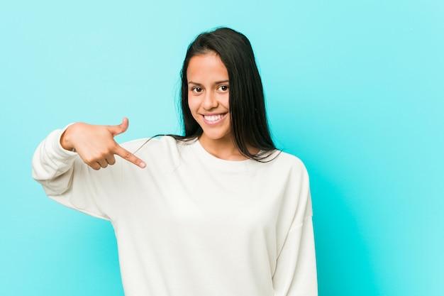 Młoda ładna latynoska kobieta wskazuje ręką ręcznie na koszulowej kopii przestrzeni, dumny i ufny