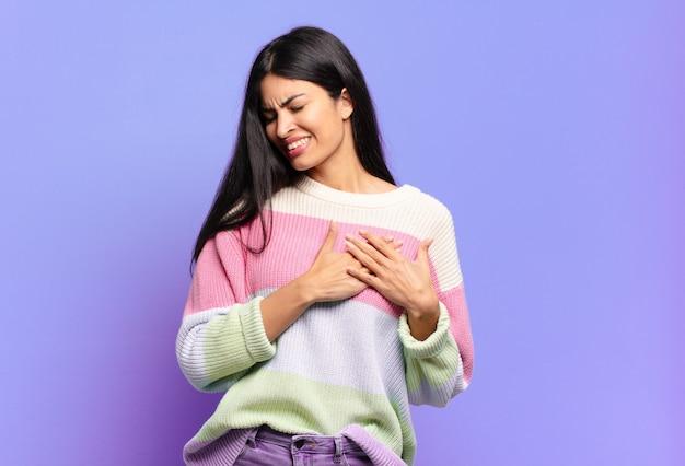 Młoda ładna latynoska kobieta wyglądająca na smutną, zranioną i załamaną, trzymająca obie ręce blisko serca, płacząc i czując się przygnębiona