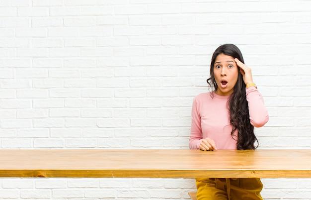 Młoda ładna latynoska kobieta wyglądająca na zaskoczoną, z otwartymi ustami, zszokowana, realizująca nową myśl, pomysł lub siedzącą przed stołem