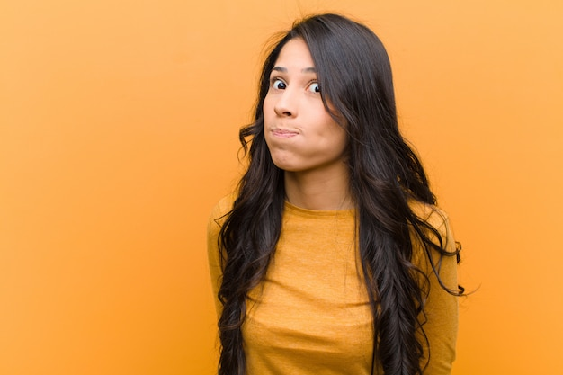 Młoda ładna latynoska kobieta z głupkowatą, szaloną, zdziwioną miną, nadymającymi się policzkami, czująca się wypchana, gruba i pełna jedzenia na brązowej ścianie