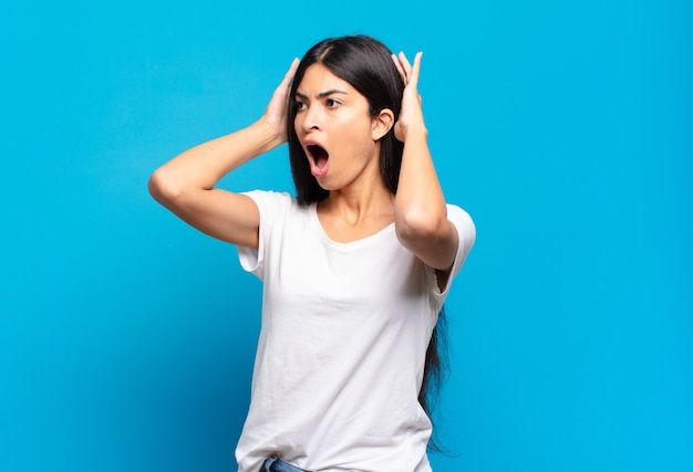 Młoda ładna latynoska kobieta z otwartymi ustami, wyglądająca na przerażoną i zszokowaną strasznym błędem, podnosząca ręce do głowy