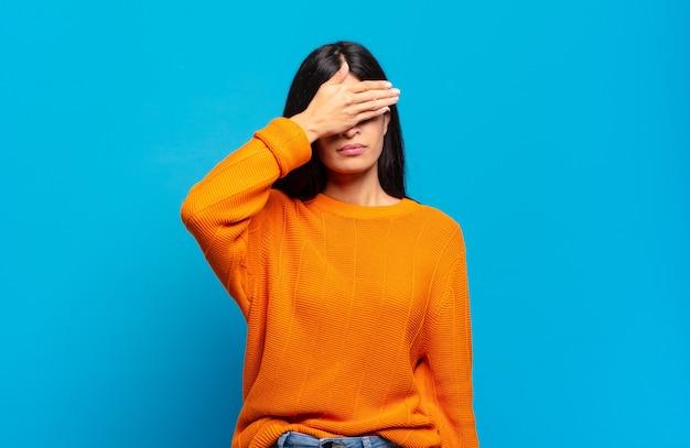 Młoda ładna latynoska kobieta zakrywająca oczy jedną ręką, przestraszona lub niespokojna, zastanawiająca się lub ślepo czekająca na niespodziankę