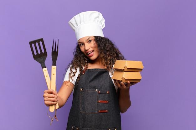 Młoda ładna latynoska kobieta. zszokowana lub zdziwiona koncepcja szefa kuchni z grilla