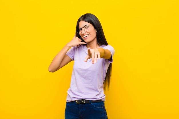 Młoda ładna latynoska uśmiechnięta wesoło i wskazująca podczas wykonywania połączenia gestem później, rozmawiając przez telefon przy płaskiej ścianie
