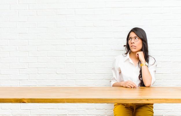 Młoda ładna latynoska wątpiąca lub myśląca, przygryzająca wargę i czująca się niepewnie i nerwowo, patrząc na copyspace po stronie siedzącej przed stołem