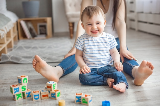 Młoda ładna matka bawić się z jej małym synem. rozochocona rodzina ma zabawę w domu z małym dziecko synem