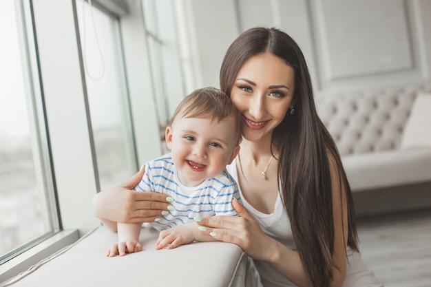Młoda ładna matka bawić się z jej małym synem. rozochocona rodzina ono uśmiecha się przy kamerą