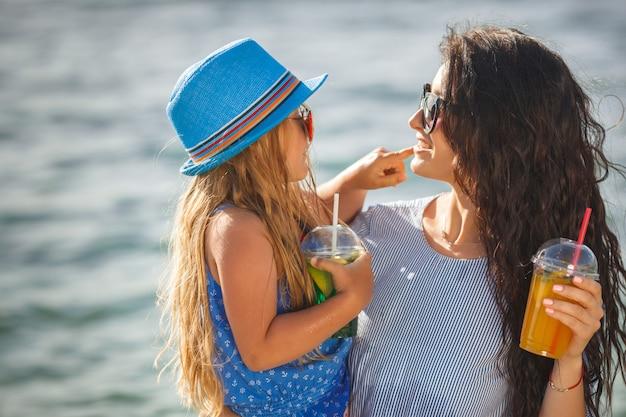 Młoda ładna matka i jej córeczka zabawy na plaży. dziewczyny piją lemoniadę.