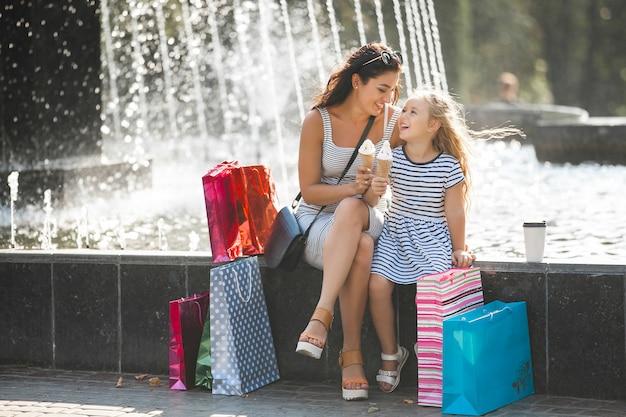 Młoda ładna matka i jej córka zabawy razem przy fontannie. piękna kobieta i jej małe dziecko je lody. wesoła rodzina zabawy.