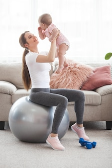 Młoda ładna matka pracuje ze swoim małym dzieckiem w domu