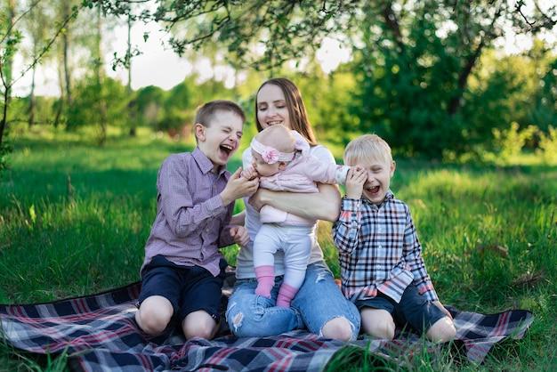 Młoda ładna matka z córką i dwoma synami na szkockiej kracie w parku. śmiech dzieci, szczęśliwe dzieciństwo
