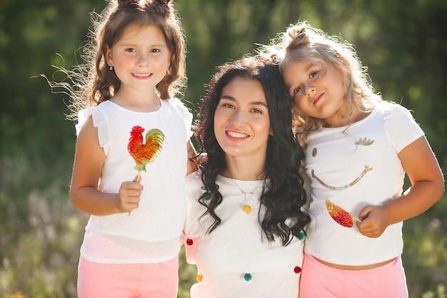 Młoda ładna matka ze swoimi uroczymi córeczkami