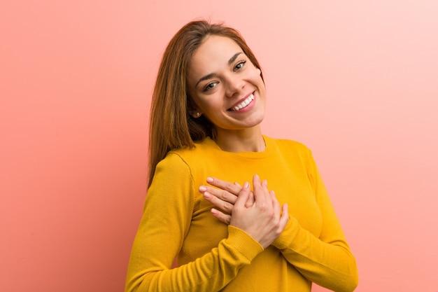 Młoda ładna młoda kobieta ma przyjazny wyraz twarzy, przyciskając dłoń do klatki piersiowej. miłość .