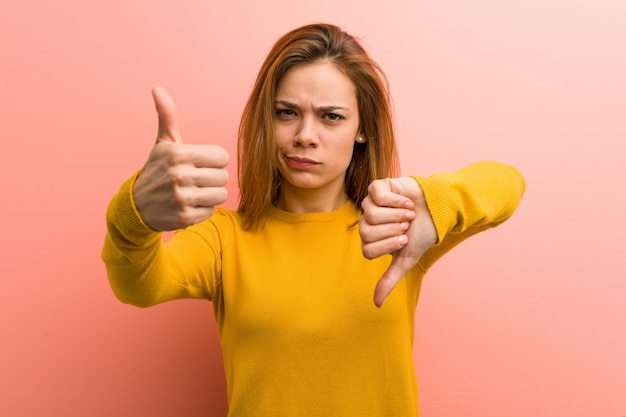 Młoda ładna młoda kobieta pokazuje kciuki w górę i kciuki w dół, trudny wybór