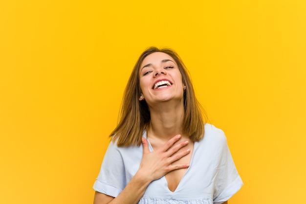 Młoda ładna młoda kobieta śmieje się głośno, trzymając rękę na klatce piersiowej.