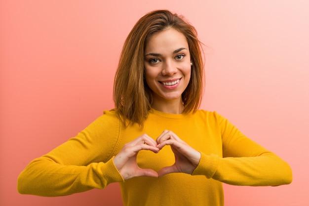 Młoda ładna młoda kobieta uśmiecha się kierowego kształt i pokazuje jej rękami.