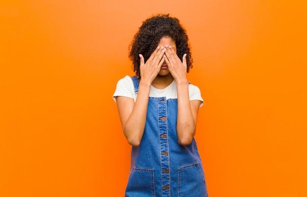 Młoda ładna murzynka czuje się smutna, sfrustrowana, zdenerwowana i przygnębiona, zakrywa twarz obiema rękami i płacze na pomarańczowej ścianie