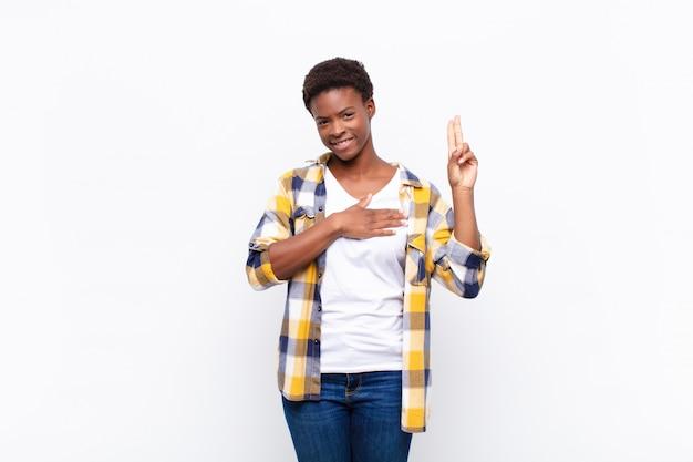 Młoda ładna murzynka wyglądająca na szczęśliwą, pewną siebie i godną zaufania, uśmiechniętą i pokazującą znak zwycięstwa, z pozytywnym nastawieniem