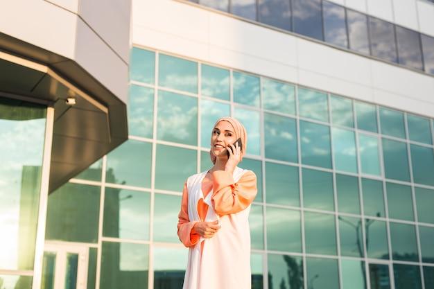 Młoda ładna muzułmańska dziewczyna w hidżabie i telefonie komórkowym