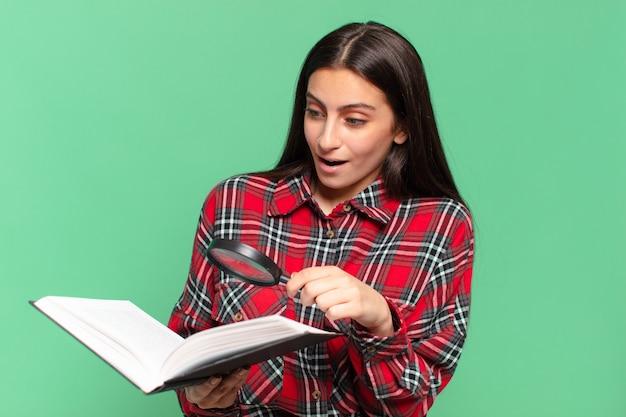 Młoda ładna nastolatka dziewczyna szuka zaskoczony. poszukiwanie w koncepcji książki