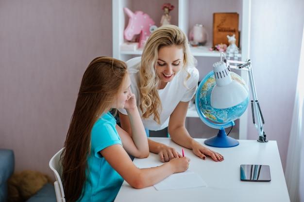 Młoda ładna nastolatka z długimi brązowymi włosami w niebieskiej sukience ćwiczy w swoim pokoju