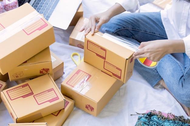 Młoda ładna nastoletnia praca w domu pisze notatce na pakuneczka pudełku. azjatyckie kobiety szczęśliwe po nowym zamówieniu od klienta, przedsiębiorcy dokonującym zakupów online w mśp lub niezależnym koncepcji pracy.