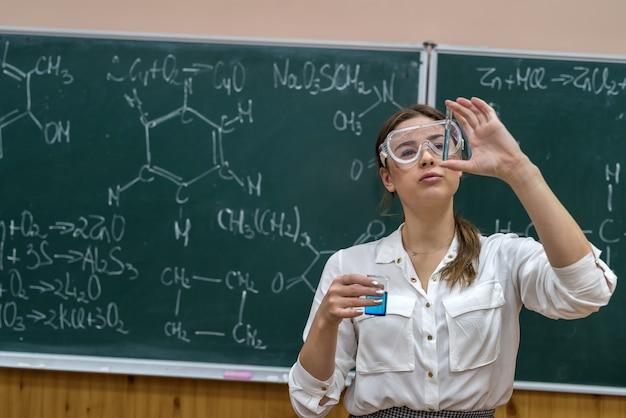 Młoda ładna nauczycielka trzyma butelkę z kolorowym płynem w pobliżu tablicy na lekcji chemii w klasie.