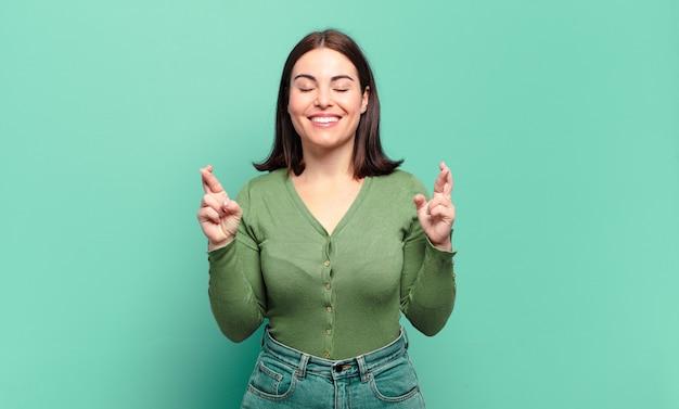 Młoda ładna niezobowiązująca kobieta uśmiecha się i niespokojnie ściska oba palce, czuje się zmartwiona i marzy lub ma nadzieję na szczęście