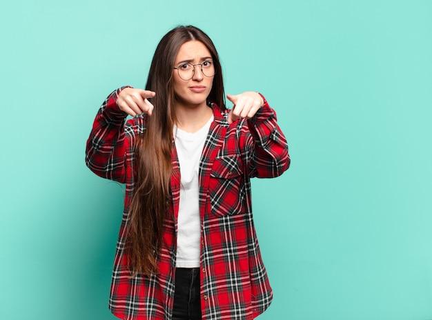 Młoda ładna niezobowiązująca kobieta wskazująca przed siebie obiema palcami i gniewnym wyrazem twarzy, mówi ci, żebyś wypełnił swój obowiązek