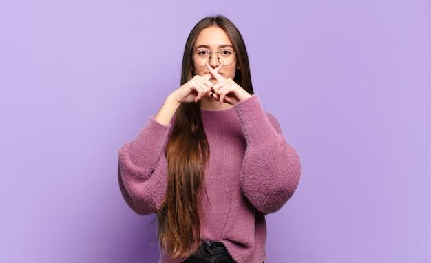Młoda ładna niezobowiązująca kobieta wyglądająca poważnie i niezadowolona z obydwoma palcami skrzyżowanymi z przodu, prosząc o ciszę
