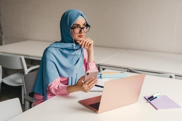 Młoda, ładna, nowoczesna muzułmanka w hidżabie, pracująca na laptopie w pokoju biurowym, edukacja online