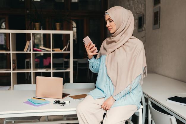 Młoda, ładna, nowoczesna muzułmanka w hidżabie, pracująca w pokoju biurowym, edukacja online