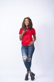 Młoda ładna pani stojąca ze skrzyżowanymi nogami, trzymająca telefon i uśmiechnięta
