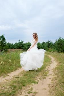 Młoda ładna panna młoda w białej sukni ślubnej kręci się wokół