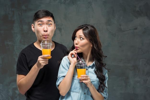 Młoda ładna para azji z kieliszkami soku pomarańczowego