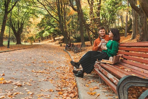 Młoda ładna para siedzi na ławce w parku, pijąc kawę, jedząc pizzę, rozmawiając ze sobą. koncepcja statku relacji