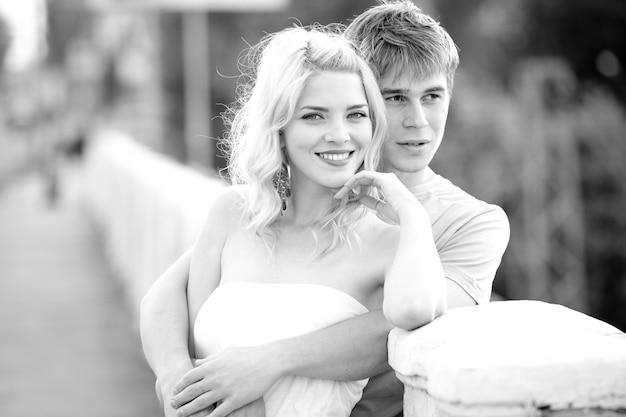 Młoda ładna para urocza dziewczyna w białej sukni i facet chodzi po moście w ciepły letni słoneczny dzień. koncepcja romantycznych spacerów