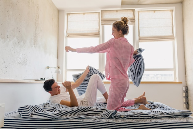 Młoda ładna para zabawy na łóżku w godzinach porannych zostaje sama w domu