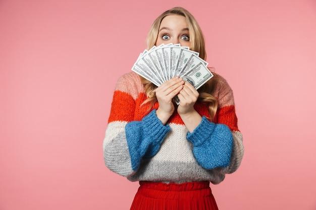 Młoda, ładna, piękna kobieta pozuje na białym tle nad różową ścianą, trzymając pieniądze zakrywające twarz