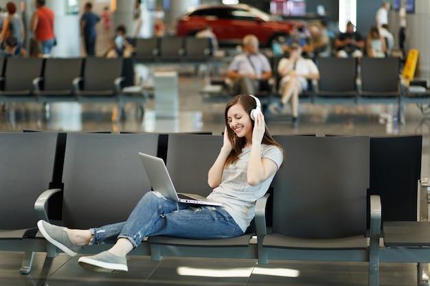 Młoda ładna podróżniczka turystyczna kobieta ze słuchawkami słuchająca muzyki pracująca na laptopie, czekaj w holu na międzynarodowym lotnisku
