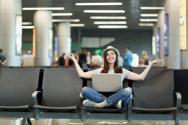 Młoda ładna podróżniczka turystyczna z laptopem siedząca ze skrzyżowanymi nogami, medytująca, rozłożona rękami, czekająca w holu na lotnisku