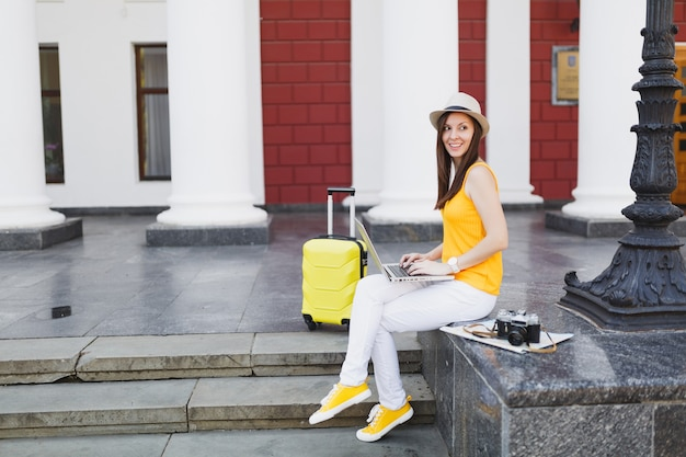 Młoda ładna podróżnik turystyczna kobieta w kapeluszu z walizką siedzieć na schodach przy użyciu pracy na komputerze typu laptop w mieście na świeżym powietrzu. dziewczyna wyjeżdża za granicę na weekendowy wypad. styl życia podróży turystycznej.